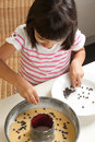 Happy little girl cooking a chocolate chip cake pouring chips to Royalty Free Stock Photography