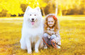 Happy little girl and dog having fun in sunny autumn day Royalty Free Stock Photo