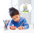 Happy little girl drawing castle with crayons Royalty Free Stock Photo