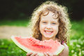 Happy little girl eating watermelon in summer park. Instagram fi Royalty Free Stock Photo