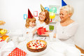 Happy little girl get present from grandmother granny gives to the with smiling mother on child birthday party with cake and Royalty Free Stock Photo