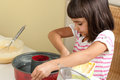 Happy little girl greasing a mold to bake a cake with butter Stock Photo