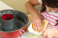 Happy little girl greasing a mold to bake a cake with hand focus on hand into the butter Stock Photo