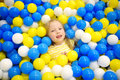 Happy little girl having fun in ball pit in kids indoor play center. Child playing with colorful balls in playground ball pool. Royalty Free Stock Photo