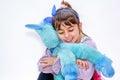 Happy little girl holding blue unicorn toy isolated on white