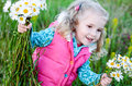 Happy little girl holding a bouquet of daisies standing in field Royalty Free Stock Images
