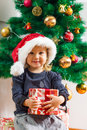 Happy Little Girl Holding a Christmas Gift Stock Photos