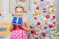 Happy little girl holding a Christmas gift and standing near Christmas trees Royalty Free Stock Photo