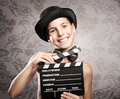 Happy little girl holding a movie clapper board on grey background Royalty Free Stock Photography