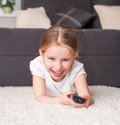 Happy little girl holding remote control Royalty Free Stock Photos
