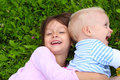 Happy little girl hugging her brother and laughing in summer on green grass Stock Photography