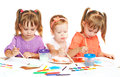 Happy little girl in kindergarten draw paints on white background sister a Royalty Free Stock Image
