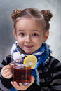 Happy little girl large cup hot lemon tea wearing warm clothes Stock Photo