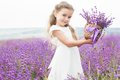 Happy little girl in lavender field with basket of
