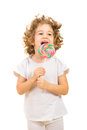 Happy little girl licking a large lollipop girlw ith curly hair isolated on white background Stock Photography