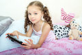 Happy little girl lying on bed with tablet computer Royalty Free Stock Photo