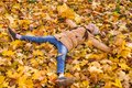 Image : Happy little girl lying on the fallen leaves arms outstretched and holding the bouquets of yellow maple leaves in her hands tag bokeh poppies