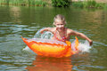 Happy little girl on orange mattress in lake at summer Stock Photos