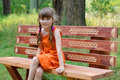 Happy little girl in orange sits on wooden beanch at summer