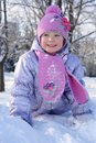 Happy little girl in pink scarf and hat crawls in snow outdoor winter Stock Photos