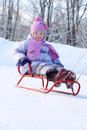 Happy little girl in pink scarf and hat goes tobogganing on snow winter Royalty Free Stock Photography