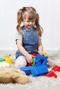Happy little girl play colorful toys on soft carpet at home Stock Photography