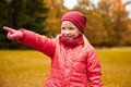 Happy little girl pointing finger in autumn park Royalty Free Stock Photo