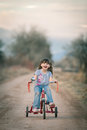 Happy little girl riding her tricycle and laughing cute classic retro Royalty Free Stock Photo