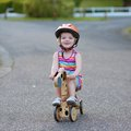Happy little girl riding tricycle on the street kid cute blonde toddler in colorful dress and orange safety helmet playing Stock Photo