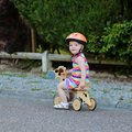 Happy little girl riding tricycle on the street kid cute blonde toddler in colorful dress and orange safety helmet playing Royalty Free Stock Photography
