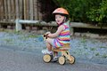 Happy little girl riding tricycle on the street kid cute blonde toddler in colorful dress and orange safety helmet playing Royalty Free Stock Images