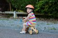 Happy little girl riding tricycle on the street kid cute blonde toddler in colorful dress and orange safety helmet playing Stock Photography