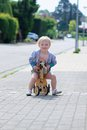 Happy little girl riding tricycle on the street kid cute blonde toddler playing outdoors her push bike wooden horse with three Royalty Free Stock Image