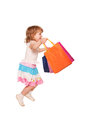 Happy little girl running and jumping with shopping bags isolated on white background Stock Image