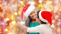 Happy little girl in santa hat hugging her mother Royalty Free Stock Photo