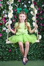 Happy little girl with shamrocks on head in green sit on swing garden next to verdant fence Stock Photo