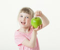 Happy little girl showing a green apple Royalty Free Stock Photo