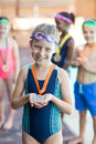 Happy little girl showing medal at poolside Royalty Free Stock Photo