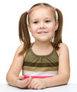 Happy little girl sits at a table and smile Stock Image