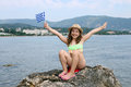 Happy little girl sitting on a rock by the sea Royalty Free Stock Photo