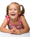 Happy little girl is sitting at the table Royalty Free Stock Images