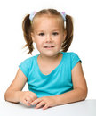 Happy little girl is sitting at the table Stock Images