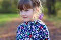 Happy little girl smiles in sunny green park Royalty Free Stock Photo