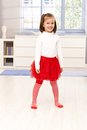 Happy little girl standing in middle of room living smiling Royalty Free Stock Images