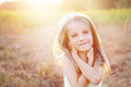 Happy little girl on summer meadow smiling a sunny field Stock Photo