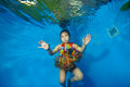 Happy little girl swimming and dancing underwater in the pool in costume for carnival on a blue background Royalty Free Stock Photo