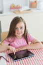 Happy little girl using tablet computer at kitchen table Royalty Free Stock Photo