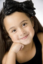 Happy little girl very resting fave on her hand black ribbon in her hair Royalty Free Stock Photos