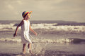 Happy little girl walking at the beach in hat on day time Stock Photos
