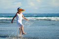 Happy little girl walking at the beach in hat day time Royalty Free Stock Photo
